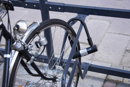 Bike locked securely via u-lock in bicycle parking area. Back right side view of front wheel. Security, stolen bike.