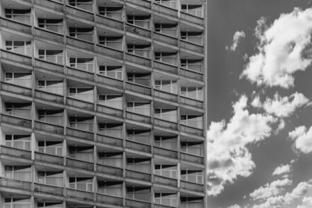 Top view of block of flats from bottom. Standardized apartments, housing, hotel. Black and white shot of architecture.