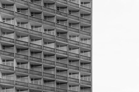 Top view of block of flats from bottom. Standardized apartments, housing, hotel. Black and white shot of architecture. Space for text 免版税图像