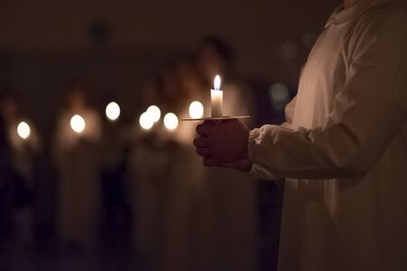 Boys are handling candles in the traditionall religious habit dresses in the church. Celebration of Lucia day in Sweden.