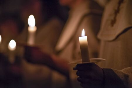 Kids are handling candles in the traditionall religious habit dresses in the church. Celebration of Lucia day in Sweden.