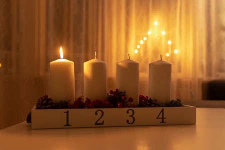 First advent light, four white candles on table with electic advent candlestick on background, the christmas period Stok Fotoğraf