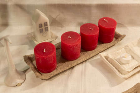 Four red advent candles on table with christmas decoration on background, the christmas period, adventsljusstake