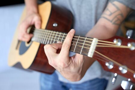 close up acoustic guitar in musician hands, small depth of field