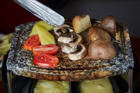 Swiss raclette. A table filled with ingredients. 免版税图像