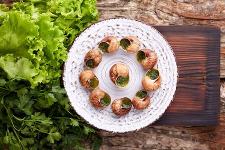 Escargots de Bourgogne - Snails with herbs butter on wooden background. Salad. Parsley.