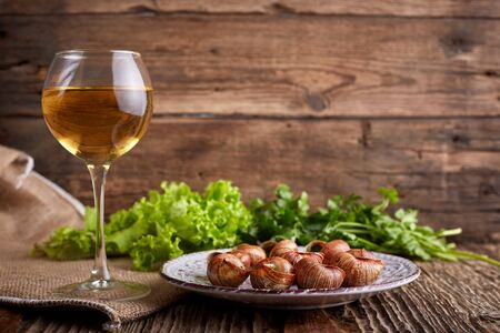 Escargots de Bourgogne - Snails with herbs butter on wooden background. Salad. Parsley. Glass of wine. 免版税图像 - 130660752