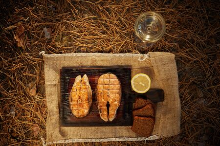 Cooked salmon steaks and ingredients on a old wooden board