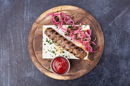 Lula kebab with a red onion and salade, traditional Caucasian dish.