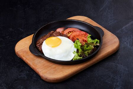Pan winth fried egg, sliced tomatoes, salad and cutlet Фото со стока