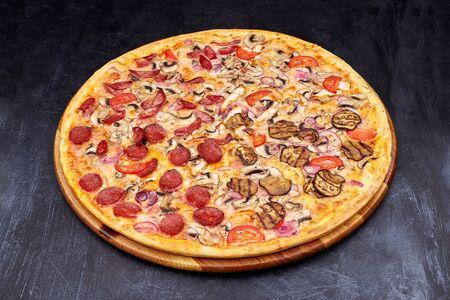 Pizza Four Seasons on wooden board on black concrete