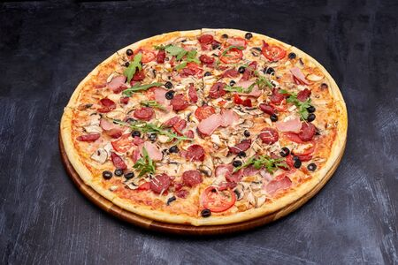 Fresh pizza Campania on wooden cutting board. isolated on dark background. 版權商用圖片