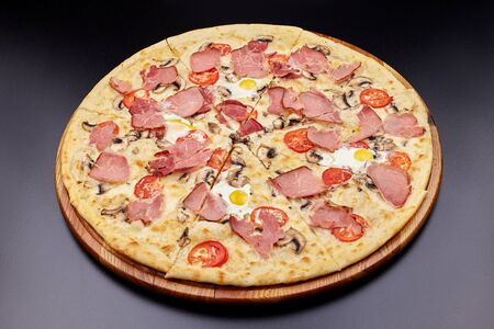 Carbonara pizza with bacon and egg on beautiful grey table. Isolated on dark background.