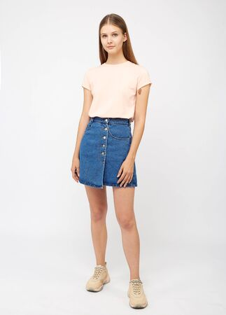 Teenager girl in a denim blue skirt on a white background.