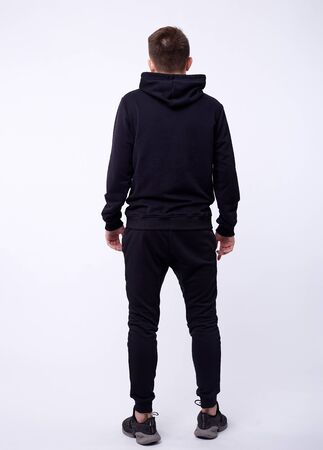 Isolated portrait of handsome serious young man in black hoodie standing with his hands in pockets. Concept of hacking and fashion Stock Photo
