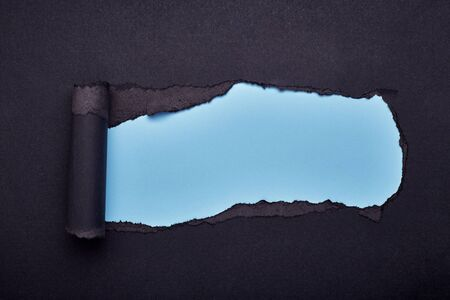 Hole in the black paper. Torn. Blue paper background. Abstract background.