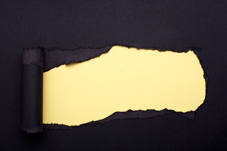 Hole in the black paper. Torn. Yellow paper background. Abstract background. Stockfoto - 133864895