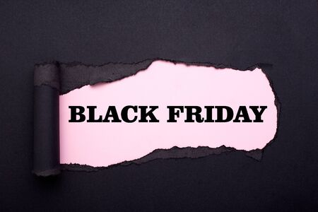 Black friday. Hole in the black paper. Torn. Pink paper background. Abstract background. Stockfoto