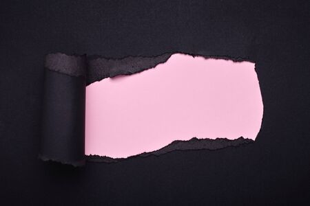 Hole in the black paper. Torn. Pink paper background. Abstract background. Stockfoto - 133828466
