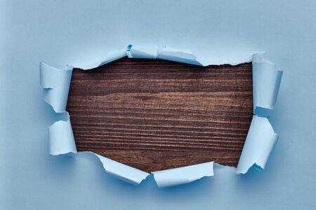 Hole in the blue paper. Torn. Black wooden background. Abstract background Stockfoto - 133828467