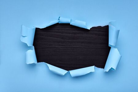 Hole in the blue paper. Torn. Black wooden background. Abstract background