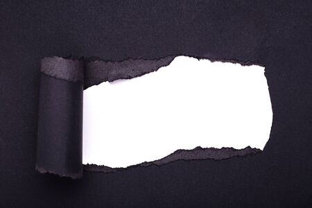 Hole in the black paper. Torn. White paper background. Abstract background.