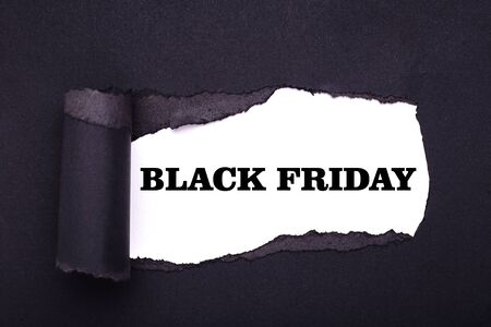 Black friday. Hole in the black paper. Torn. White paper background. Abstract background.