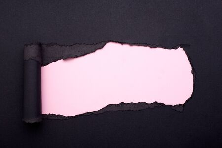 Hole in the black paper. Torn. Pink paper background. Abstract background. Stockfoto - 133828474