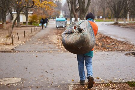 Municipal sweeper cleaning park from leaves with rakes and broomsticks.