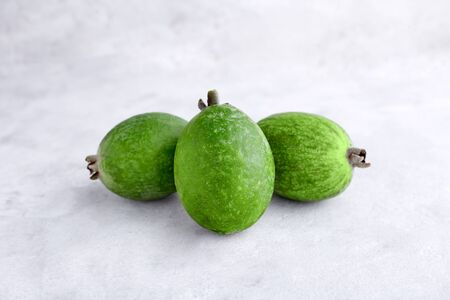 Green feijoa fruits on gray concrete background table. Tropical fruit feijoa. Set of ripe feijoa fruits.