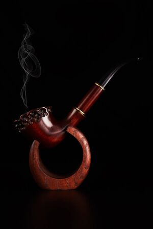 Tobacco pipe with smoke isolated on black background.