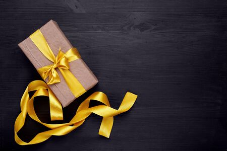 Craft paper gift box with golden, yellow ribbon bow on black wooden background. Copy space. Gold ribbon. 免版税图像