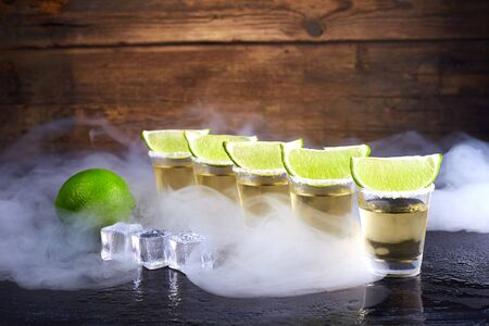 Mexican tequila gold in short glasses with salt, lime slices and ice on a wooden table. Smoke.