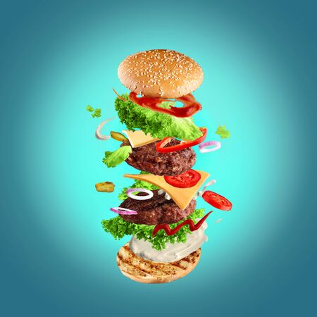 Maxi hamburger, double cheeseburger with flying ingredients isolated on blue background. High resolution image Stock Photo
