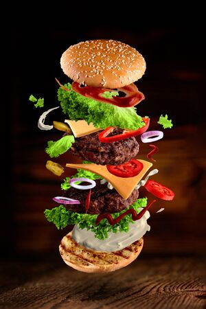 Maxi hamburger, double cheeseburger with flying ingredients isolated on wooden background. High resolution image Foto de archivo - 138199120