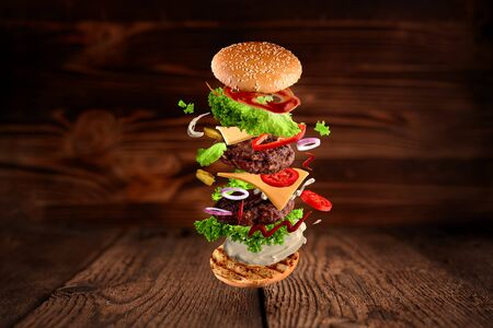 Maxi hamburger, double cheeseburger with flying ingredients isolated on wooden background. High resolution image