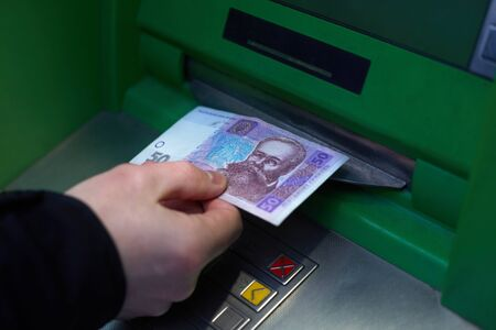Male hand while withdrawing 50 Ukrainian hryvnia from an ATM. The depreciation of the national currency, the hryvnia. Stock Photo