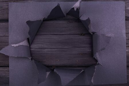 Big hole in the black paper. Torn. Black wooden background. Abstract background. Stockfoto