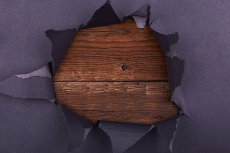 Big hole in the black paper. Torn. Wooden background. Abstract background.