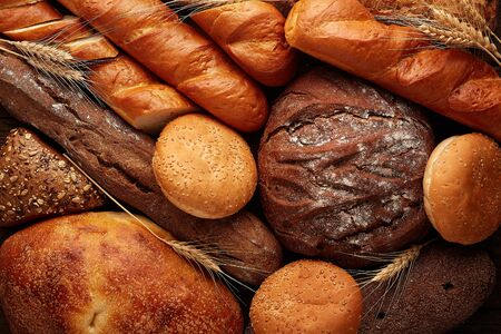 Different bread and bread slices. Spikelets of wheat. Food background.