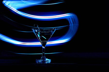 Martini cocktail drink splash with ice cubes in neon iridescent . Minimal night party life concept. Zdjęcie Seryjne