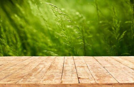 Mockup. Empty wooden deck table with foliage bokeh background. Archivio Fotografico