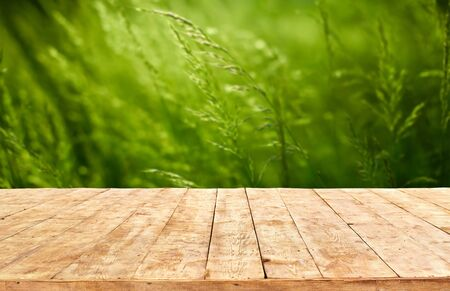 Mockup. Empty wooden deck table with foliage bokeh background. Stockfoto