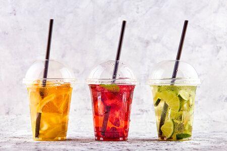 Lemonade to go. Three cups with mint, cherry, strawberry, kiwi, lime, orage, lemon on concrete background. Foto de archivo