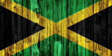 Flag of Jamaica painted on grungy wood plank background 스톡 콘텐츠
