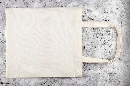 Blank cotton tote bag, design mockup. Handmade shopping bag on concrete table. Mockup. Banco de Imagens