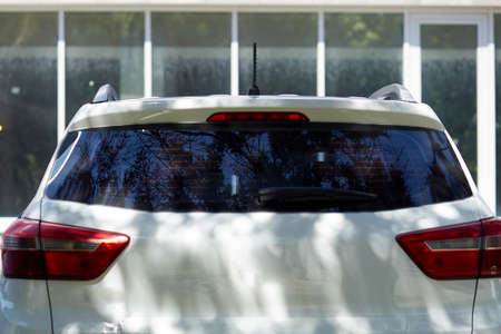 Back window of white car parked on the street in summer sunny day, rear view. Mock-up for sticker or decals
