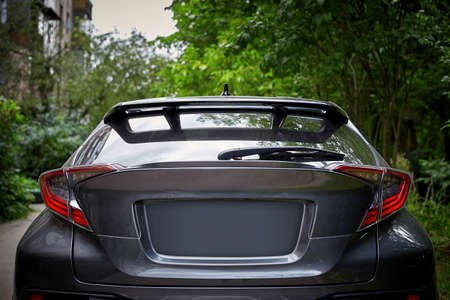 Back window of black car parked on the street in summer sunny day, rear view. Mock-up for sticker or decals