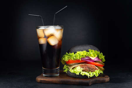 Big single cheeseburger with glass of cola on dark background
