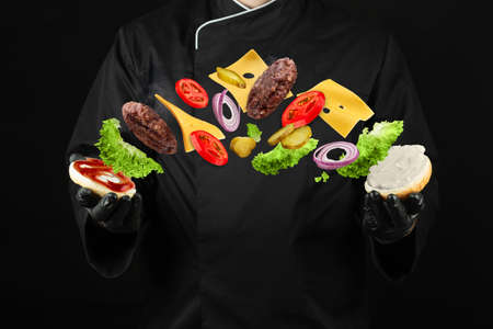 Chef on black background with flying burger in his hands 版權商用圖片